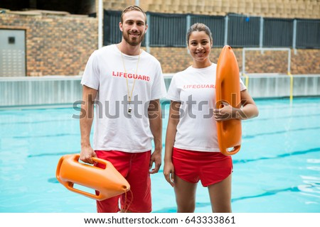 Portrait of two lifeguards standing with rescue buoy at poolside Сток-фото ©