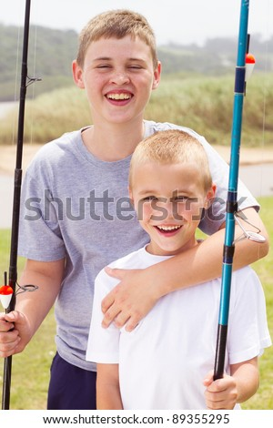 portrait of two little boys fishing by the lake