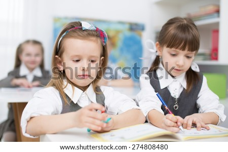 Portrait of two little girls looking at camera at workplace with children on background