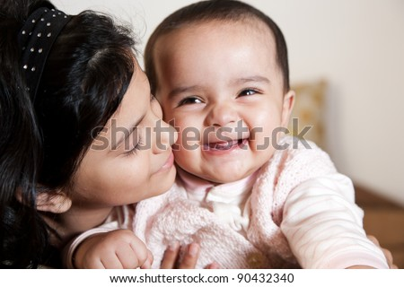 portrait of two little muslim girls, happy little girl holding her baby sister