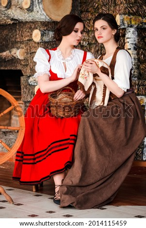 Portrait of Two Lovely Smiling Caucasian Ladies  Posing With Spinning Wheel And Fancywork Hoop in Retro Dress In Rural Environment.Vertical Shot Stock photo ©