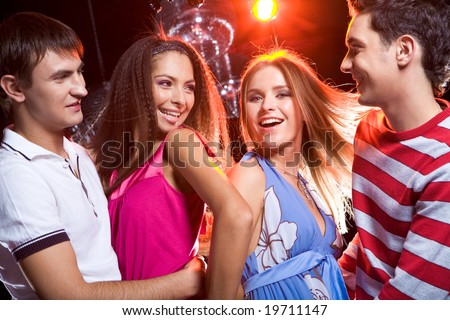 Portrait of two loving couples dancing at disco together