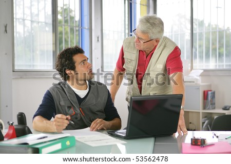 Portrait of two men in front of a laptop computer in an office