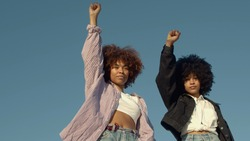 portrait of two mixed-race women with huge afro hair makes a protest black raised fist gesture outdoors portrait on the sky background