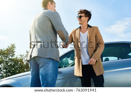 Portrait of two modern young men greeting each other shaking hands outdoors standing next to expensive car against clear blue sky