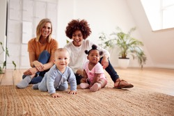 Portrait Of Two Mothers Meeting For Play Date With Babies At Home In Loft Apartment