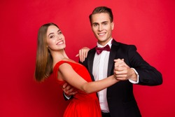 Portrait of two nice sweet lovely attractive adorable gorgeous charming cheerful positive affectionate people married spouses wife husband dancing isolated over bright vivid shine red background
