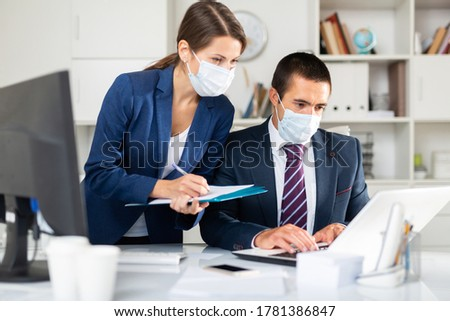 Portrait of two office employees in medical masks concentrating on work with papers and laptop. Necessary precautions during coronavirus pandemic