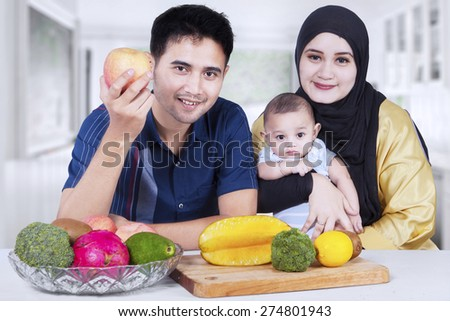Portrait of two parents sitting at home with their little son and fresh fruit on the table