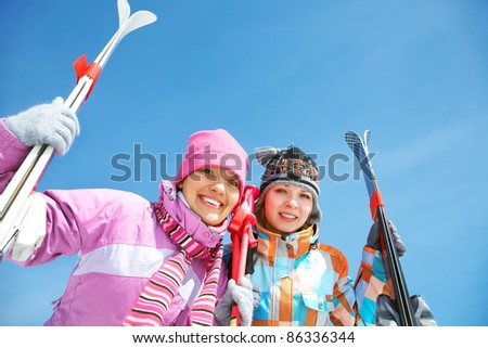 Portrait of two pretty girls with skis