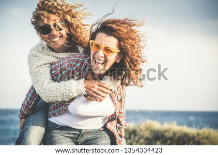 Portrait of two pretty woman enjoy free time. Smiling middle age girls giving her laughing friend piggyback while enjoying the day together at the beach. Best friends smiling and playing together #1354334423
