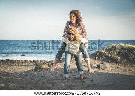 Portrait of two pretty woman enjoy free time. Smiling middle age girls giving her laughing friend piggyback while enjoying the day together at the beach. Best friends smiling and playing together #1368716792