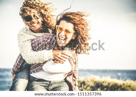 Portrait of two pretty woman enjoy free time. Smiling middle age girls giving her laughing friend piggyback while enjoying the day together at the beach. Best friends smiling and playing together