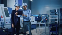 Portrait of Two Professional Engineers Use Industrial Digital Tablet to Work with Augmented Reality. Great Template Shot for Augmented Reality. Factory Workshop with CNC Machinery.