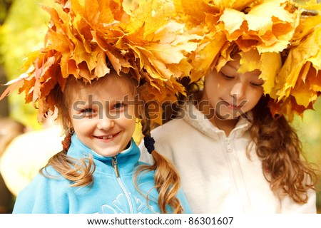 Portrait of two school aged girls wearing autumnal head wreaths
