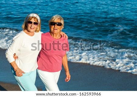 Portrait of two senior female friends in casual sportswear outdoors.