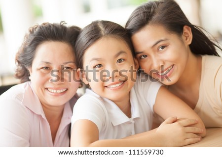 Portrait of two sisters and mother smiling at camera