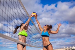 Portrait of two slim sporty girls playing beach volleyball against a bright blue sky