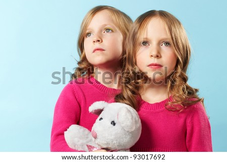 Portrait of two smart girls in crimson clothes against blue background