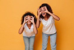 Portrait of two smiling african sisters looking through their fingers and laughing isolated over orange background
