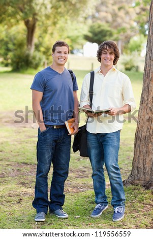 Portrait of two smiling male students posing in a park - stock photo