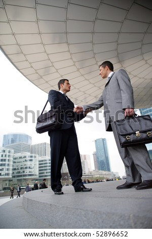 Portrait of two smiling men shaking hands
