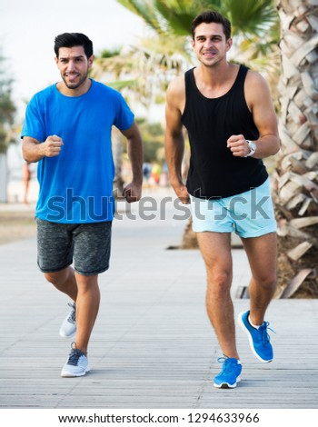 Portrait of two smiling sportsmen are jogging in time training in the park near ocean