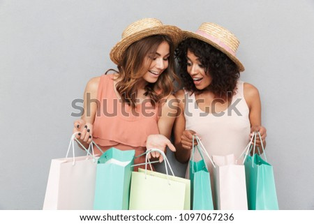 Portrait of two smiling young women dressed in summer clothes looking inside shopping bags isolated over gray background #1097067236