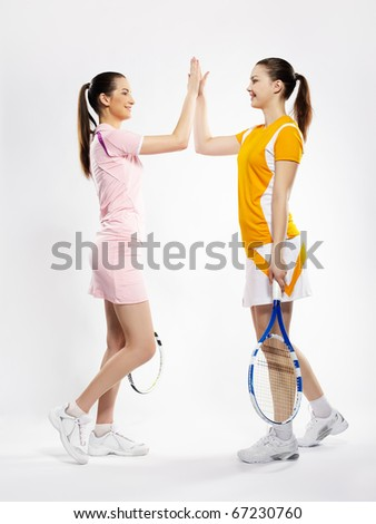 portrait of two sporty girls tennis players with rackets