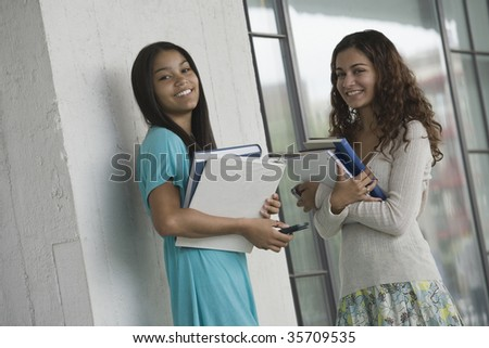 Portrait of two teenage girls holding books and smiling in a school