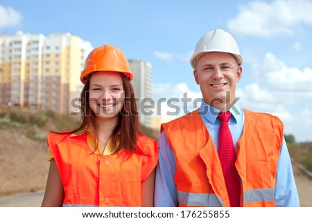 Portrait of two white-collar workers wearing protective helmet works on the building site