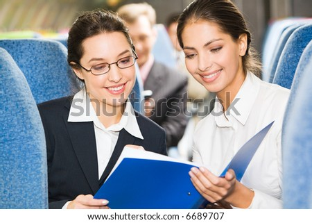 Portrait of two women discussing business plan in the plane