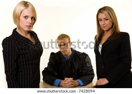 Portrait of two women lawyers in front of a male judge looking forward - stock photo