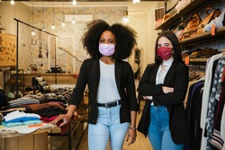 Portrait of two women owners of the clothes shop at the entrance to welcome customers during the Coronavirus Covid-19 pandemic wearing protective face masks - Millennial initiate a start-up business