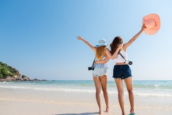 Portrait of two young asian female friends walking on the sea shore turn back at camera laughing. Multiracial young women strolling along a beach.