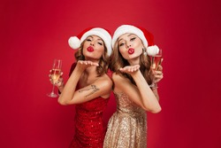 Portrait of two young attractive girls in christmas hats and dresses holding champagne glasses and sending air kiss isolated over red background