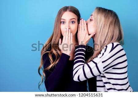 portrait of two young attractive happy girlfriends women with makeup eavesdrops whispers a secret (mystery) in the studio on a blue background. the concept of gossip and confidentiality