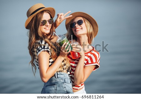 Portrait of two young beautiful girls in trendy stripe shirt, beach hat, sunglasses an jeans shirt on the sea. two friends having fun at the sea with cocktails on their hands. #696811264