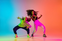 Portrait of two young beautiful hip-hop dancers in modern clothes on colorful gradient blue orange at dance hall in neon. Youth culture, movement, active lifestyle, action, street dance, ad