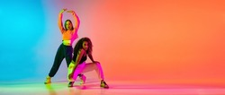 Portrait of two young beautiful hip-hop female dancers in modern clothes on colorful gradient blue orange at dance hall in neon. Youth culture, movement, active lifestyle, action, street dance, ad
