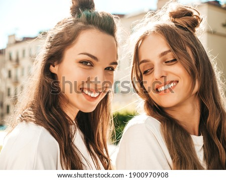 Portrait of two young beautiful smiling hipster female in trendy summer white t-shirt clothes.Sexy carefree women posing on street background. Positive models having fun and hugging
