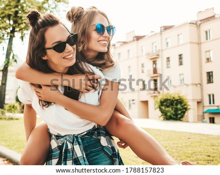 Portrait of two young beautiful smiling hipster girls in trendy summer white t-shirt clothes.Sexy carefree women posing on street background. Positive model sitting on her friend's back