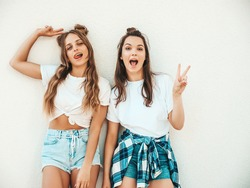 Portrait of two young beautiful smiling hipster women in trendy summer white t-shirt clothes.Sexy carefree women posing on street background. Positive models having fun, hugging and going crazy
