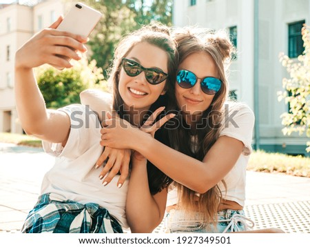 Portrait of two young beautiful smiling hipster women in trendy summer white t-shirt clothes.Sexy carefree women posing on street background. Positive models having fun, hugging and taking selfie
