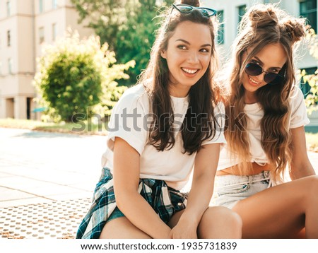 Portrait of two young beautiful smiling hipster women in trendy summer white t-shirt clothes.Sexy carefree women posing on street background. Positive models having fun, hugging