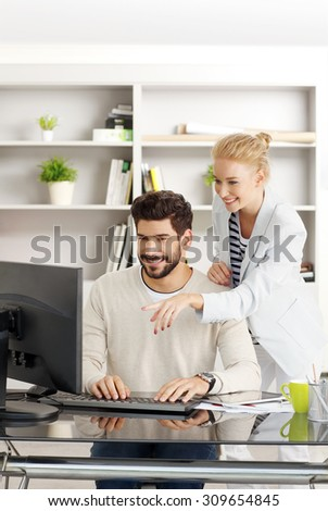 Portrait of two young business people working together at office. Professional man sitting in front of monitor and typing presentation while creative female standing next to him and consulting.