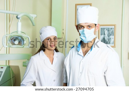 portrait of two young doctors looking at camera in dentistry office