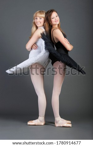 Portrait of two young female ballet dancers standing back to back over grey background Сток-фото ©