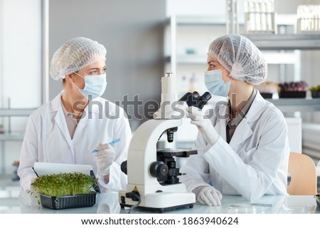 Portrait of two young female scientists looking in microscope while studying plant samples in biotechnology lab, copy space ストックフォト ©
