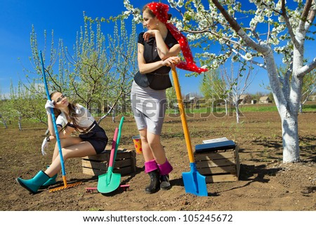 Portrait of two young females with rakes and spade on garden